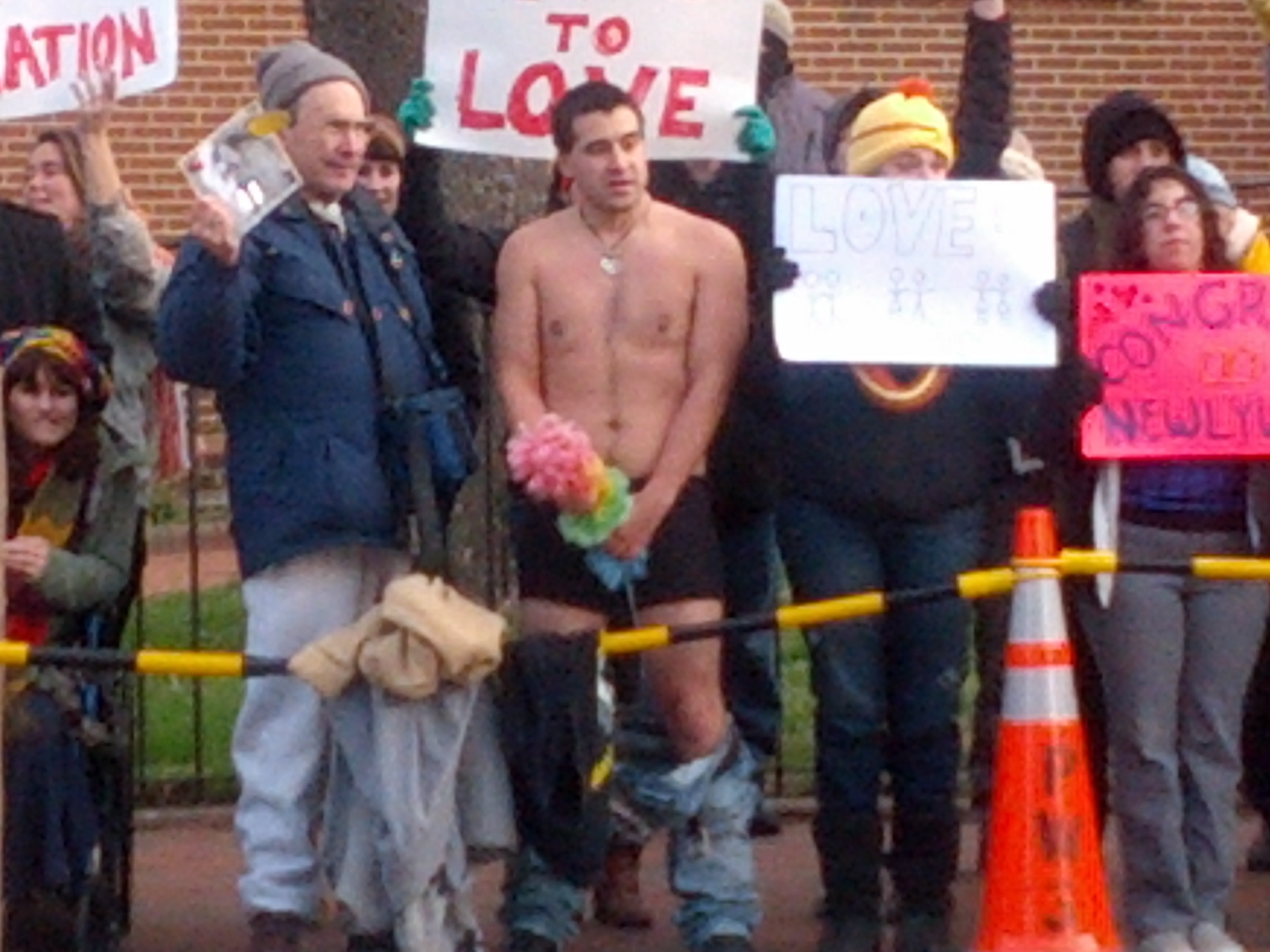 A counter protester naked except for his underwear holds a furry, rainbow-colored pole in front of his groin.