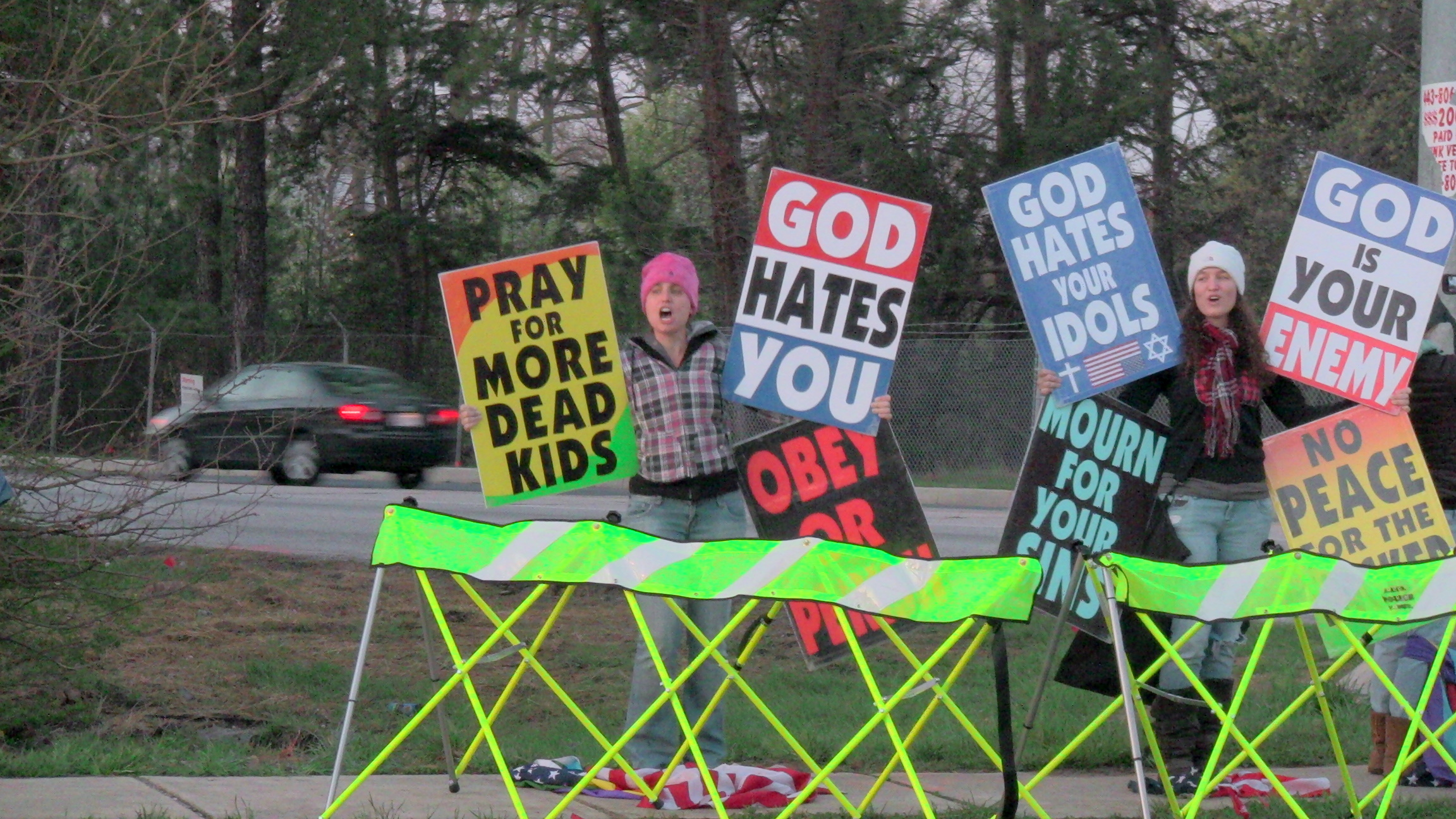 A Westboro Baptist Church Demonstrator Standing on an American Flag